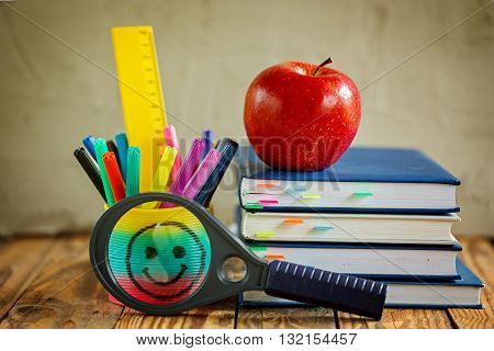 Group of school supplies and books and red apple over on background.School stationary equipment.