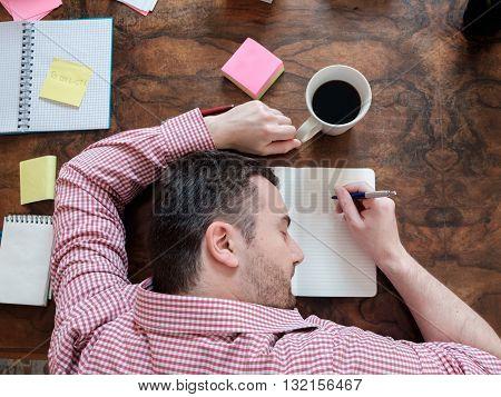 portrait of exhausted worker sleeping on his desktop