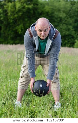 Man Exercising With 3 Kilos Medicine Ball Outdoors