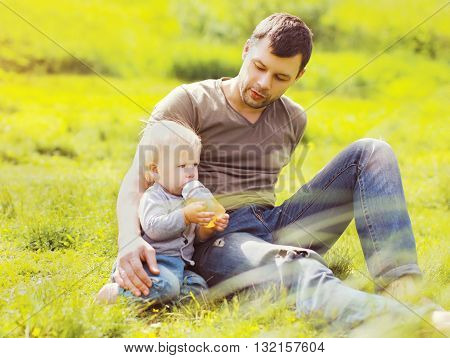 Father And Baby Drinks From A Bottle Sitting On Grass Summer