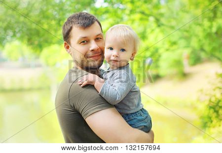 Portrait Happy Father And Son On Hands In Summer Day