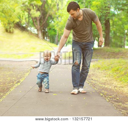 Young Father And Son Walking Together In Summer Park