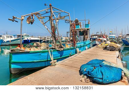Old colorful fisherman boat tied to a pier in port of old jaffa in Israel.