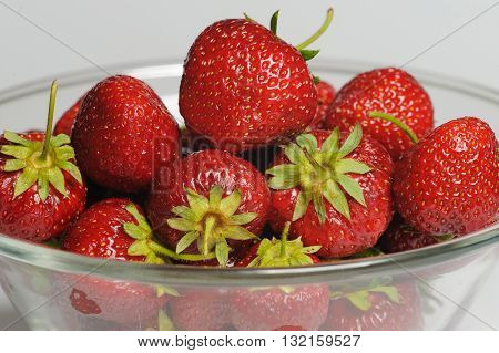 Juicy, tasty strawberry on the glass plate. Strawberries in a glass plate on white background. Close-up fresh strawberries lay on glass plate.