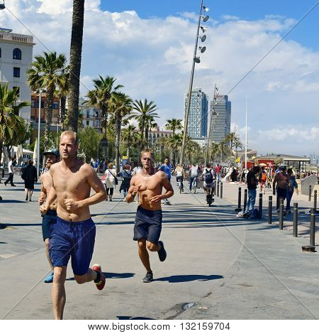 BARCELONA, SPAIN - MAY 30: People jogging and walking in the seafront of La Barceloneta on May 30, 2016 in Barcelona, Spain. The city has a long and busy seafront