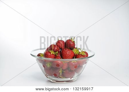 Juicy, tasty strawberry on the glass plate. Strawberries in a glass plate on white background with copy space. Fresh strawberries lay on glass plate.