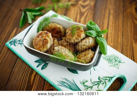 fried cutlet in ceramic form on a wooden table