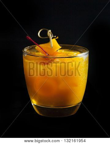 Golden Sour alcohol coctail tropic and brite on black background made of scotch whiskey mango puree hohey syrup egg white and lime juice