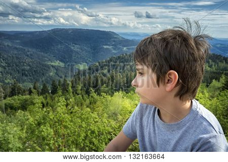 Portrait of a schoolboy on a background of mountain landscape