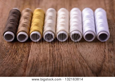 cotton sewing from white to brown on wood