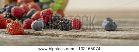 Panoramic view of mixed berry fruits scattered on a textured rustic wooden desk.