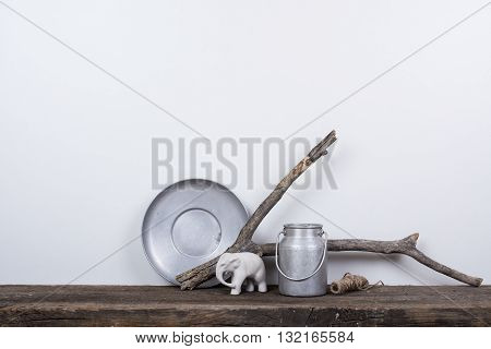 Scandinavian style home decor with natural wood, rustic vintage board and white wall background.