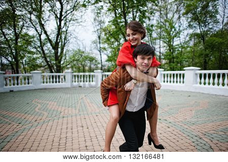 Happy Couple Walking In Love. Stylish Man At Velvet Jacket Rolls His Girl On His Back.