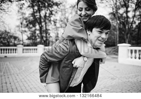 Happy Couple Walking In Love. Stylish Man At Velvet Jacket Rolls His Girl On His Back. Black And Whi
