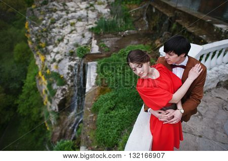 Couple Hugging In Love Background Fantastic Cliff With Waterfall. Stylish Man At Velvet Jacket And G