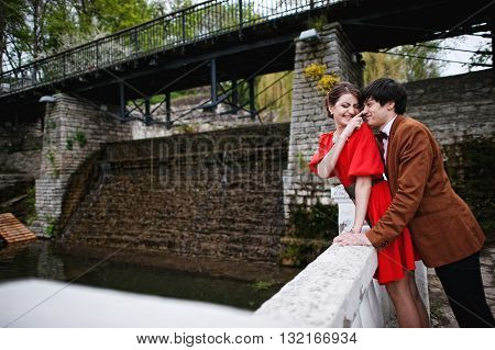 Couple Hugging In Love Background Water Dam. Stylish Man At Velvet Jacket And Girl In Red Dress In L