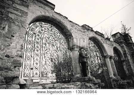 Couple Hugging In Love Background Old Gates Of Castle. Stylish Man At Velvet Jacket And Girl In Red