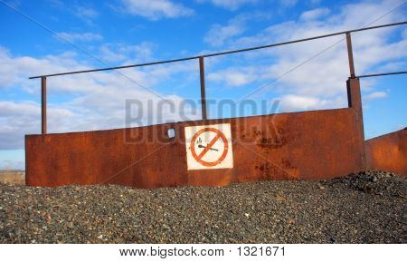 No Fire And Smoking Sign On Rusty Board In Stone Desert