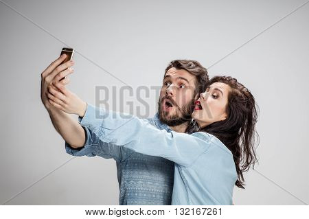 Portrait of happy couple on gray background. Attractive man and woman doing selfie photo