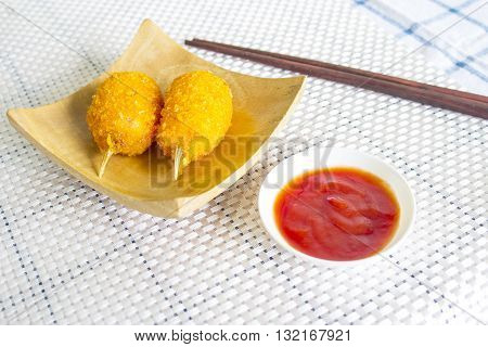 Crab tempura on a wooden plate with tomato sauce