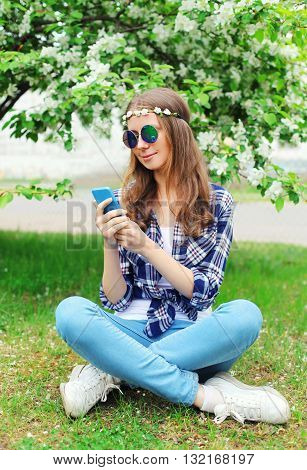Beautiful Hippie Woman Using Smartphone Sitting On Grass In Flow