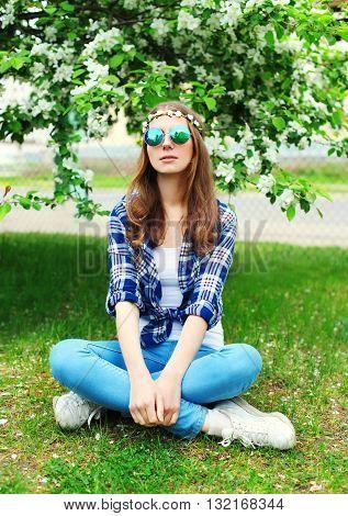 Fashion Cool Hippie Woman Sitting Resting On Grass In Flowering Garden