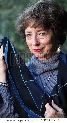 Mature female senior fashion model expressions outside.