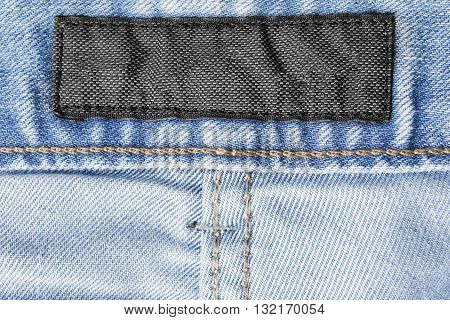 Blank clothes label on blue denim as a background