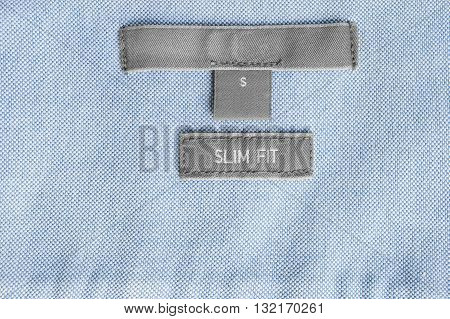 Clothes label lettered slim fit on blue cloth as a background