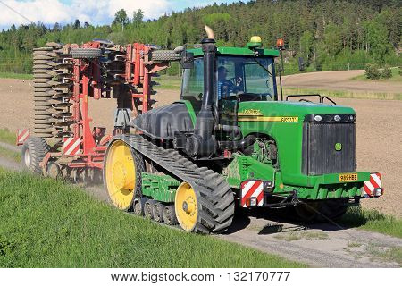 SALO, FINLAND - MAY 27, 2016: John Deere 9520T agricultural crawler tractor and cultivator moving along rural road on the way to cultivate a stubble field at spring.