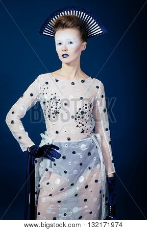 Creative shocking portrait of Japanese young woman in fashion elegant designers grey dress and blue velvet gloves on blue blackground