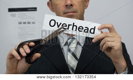 Male office worker or businessman in a suit and tie cuts a piece of paper with the word overhead on it as an overhead reduction business concept.