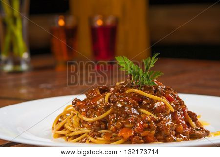Traditional italian Bolognese with spaguetti over a wooden table