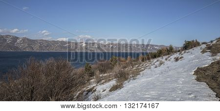 Panoramic view of Sevan Lake with snow maintains around of it