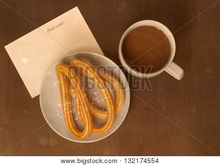 Toned retro style photo of plate of churros traditional Spanish (especially Madrid) dessert (especially for Sunday breakfast) with cup of hot chocolate and blank postcard with copyspace