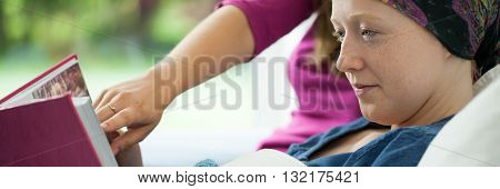 Girl With Cancer Holding Photo Album