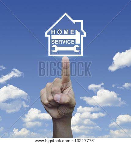Hand pressing hammer and wrench with house icon over blue sky with white clouds background Home service concept