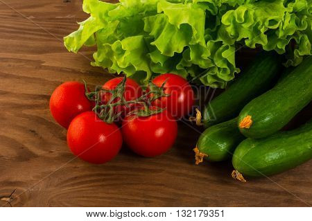 Cucumber and cherry tomato on wooden background. Tomato. Cucumber. Ripe vegetables. Fresh vegetables. Cherry tomato. Healthy eating. Vegetables.