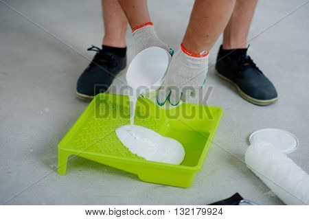 The yellow tray and the roller for painting lie on a gray concrete floor. Hands in gloves pour into a tray paint from can. Strong male legs of the worker are visible.