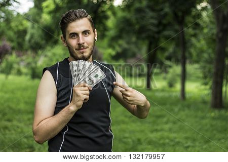 Man with a lot of dollars in the park