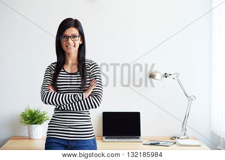 Smiling Attractive Young Woman Standing Near The Window With Arms Crossed