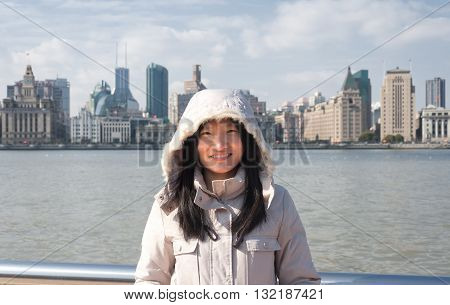 A chinese woman wearing a winter coat on the Huangpu River with the historic bund in the background in Shanghai China.
