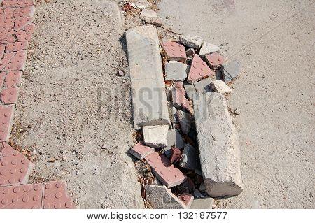 Concrete blocks and tile pieces on a broken sidewalk