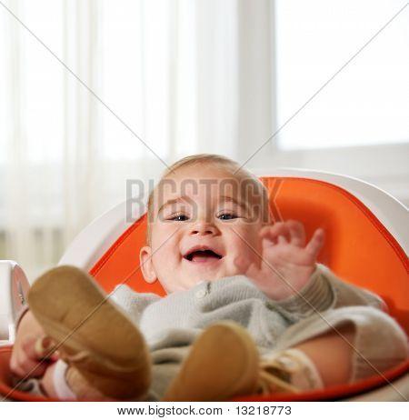 Sentado em uma cadeira de criança feliz