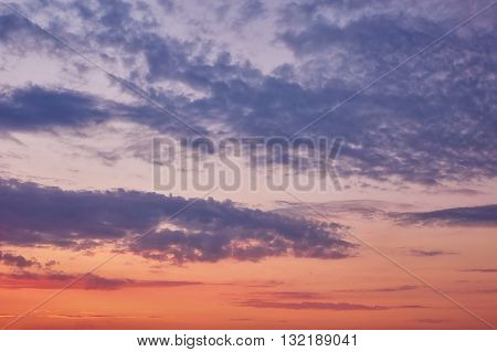 Beautiful cloudy evening sky with sun rays with purple tinge