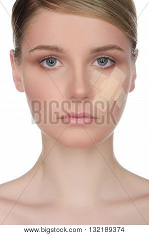 Young woman with medical plaster on her face isolated on white