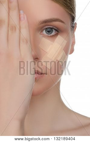 face of beautiful woman with medical patch isolated on white