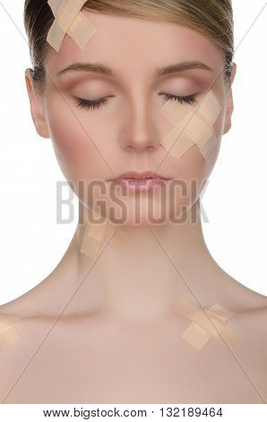 European woman with medical plaster on her face isolated on white