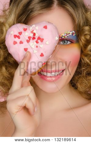 beautiful woman with donut in face on pink background