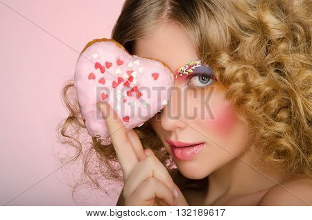 European woman with donut in face on pink background